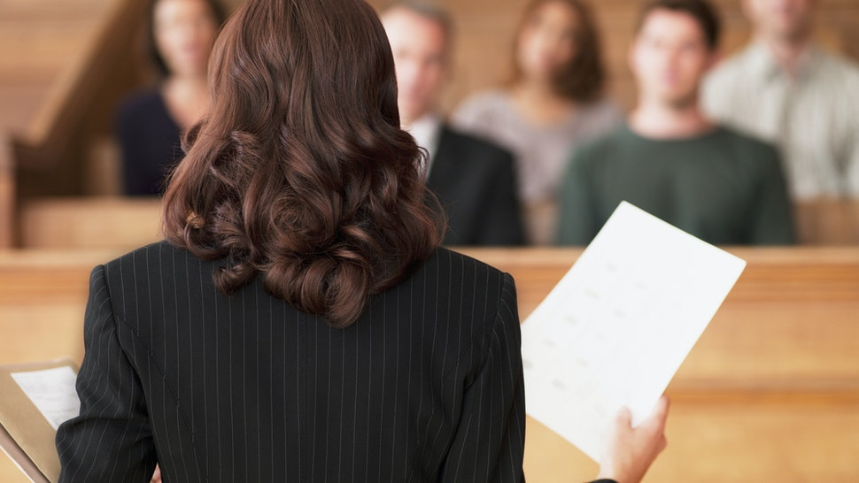 Lawyer holding document and speaking to jury in courtroom - stock photo