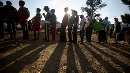 Central American migrants, taking part in a caravan heading to the US, queue to receive a meal at a temporary shelter in Irapuato, Guanajuato state, Mexico on November 11, 2018. - The trek from tropical Central America to the huge capital of Mexico is declining the health of the migrant caravan that endures extreme climate changes, as well as overcrowding and physical exhaustion, and still has to face the desert that leads to the United States. (Photo by ALFREDO ESTRELLA / AFP) (Photo credit should read ALFREDO ESTRELLA/AFP via Getty Images)