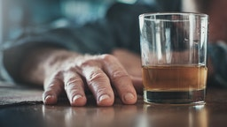 Hand by glass of liquor, man's head on table - stock photo