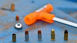 9mm. rounds, including the catridge of a decoupled bullet, wait to be loaded into a hand-held pistol at a firing range to demosntrate the inert effect of the separated-bullet when fired at Kenya's National Gun Owners Association