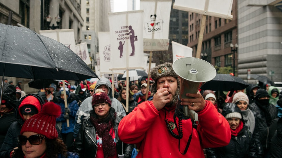 Braving snow and cold temperatures, thousands marched through the streets near City Hall during the 11th day of an ongoing teachers strike on October 31, 2019 in Chicago, Illinois.