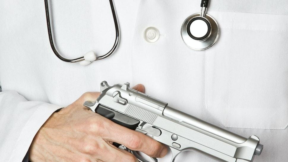 Doctor holding handgun - stock photo