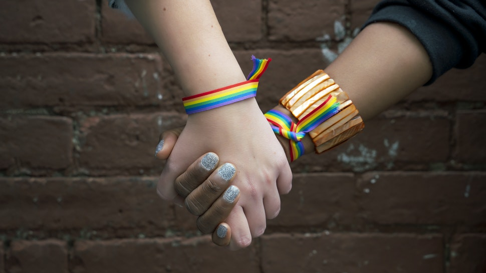 Multiracial gay couple holding hands in Brooklyn - stock photo
