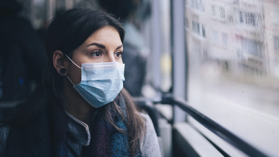 Young woman wearing protective face mask, she sitting in bus transportation in the city.