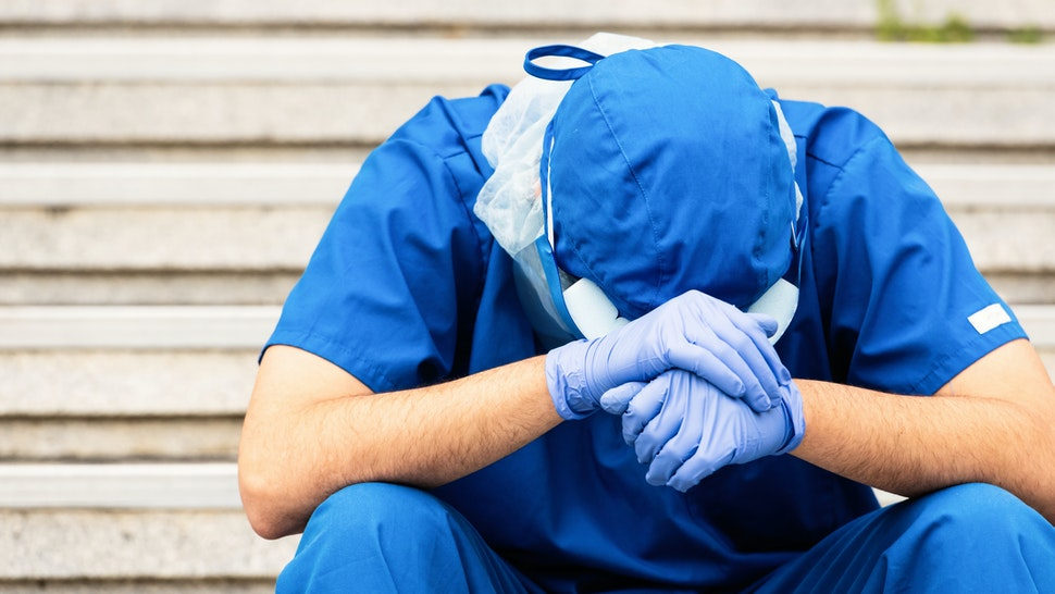 Serious, overworked, very sad male health care worker - stock photo