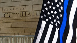 A Thin Blue Line flag is waved during the Seattle Police Officers Guildâs rally to stop defunding of the Seattle Police Department on Sunday, August 9, 2020 at Seattle City Hall.