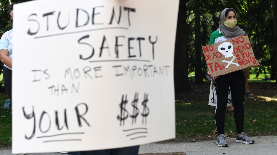 Members of the Ohio State University Graduate Student Labor Coalition hold signs during a protest on the first day of classes at Ohio State University in Columbus, Ohio, U.S., on Tuesday, Aug. 25, 2020.
