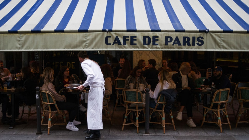 A waiter serves customers eating and drinking on the terrace area outside Cafe de Paris, ahead of the enforcement of new Covid-19 restrictions which will see bars and restaurants closing early, in Paris, France, on Monday, Sept. 28, 2020. President Emmanuel Macrons government is seeking to ease tension after the first significant tightening of restrictions on French daily life since the end of the lockdown in May. Photographer: Nathan Laine/Bloomberg via Getty Images