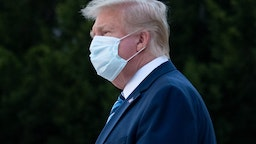 """US President Donald Trump wears a facemask as he leaves Walter Reed Medical Center in Bethesda, Maryland heading to Marine One on October 5, 2020, to return to the White House after being discharged. - Trump announced Monday he would be """"back on the campaign trail soon"""", just before returning to the White House from a hospital where he was being treated for Covid-19. (Photo by SAUL LOEB / AFP)"""