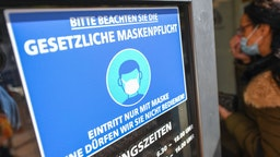 "Rhineland-Palatinate, Mainz: A woman who wears a mouth and nose protector walks up to the entrance of a bakery at a sign saying ""Please observe the legal obligation to wear a mask. Admission only with mask. Without it we are not allowed to serve you""."