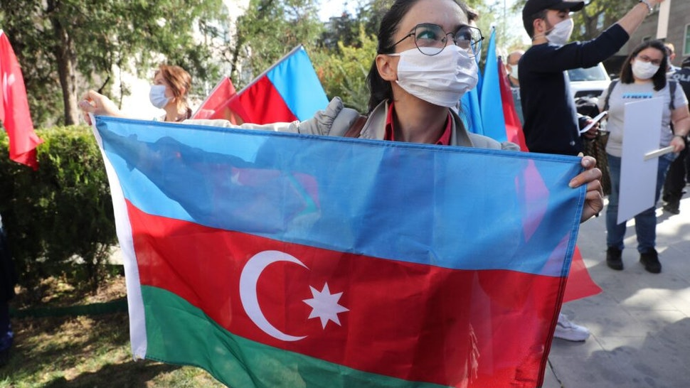 A member of Turkey and Azerbaijan Friendship Cooperation and Solidarity Foundation (TADIV) holds Azerbaijan's flag as she takes part in a protest outside the French Embassy in Ankara, Turkey on October 16, 2020. - Baku and Yerevan have for decades been locked in a simmering conflict over Nagorno-Karabakh, an ethnically Armenian region of Azerbaijan which broke away from Baku in a 1990s war that claimed the lives of some 30,000 people. The Caucasus neighbours have defied international calls to halt hostilities and accused the other of starting new clashes that began September 27 and have seen the heaviest fighting since a 1994 truce. (Photo by Adem ALTAN / AFP)