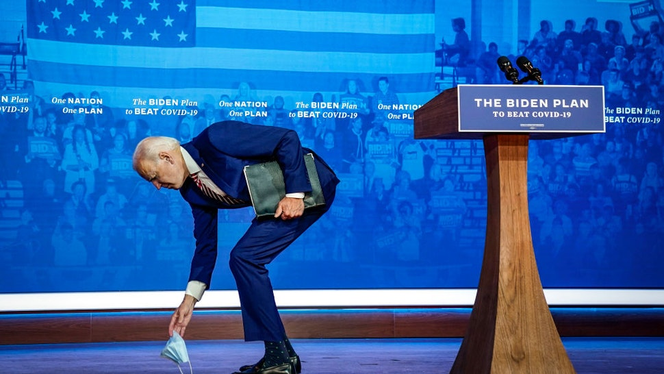 Democratic presidential nominee Joe Biden picks up his protective face mask after he dropped it while leaving the stage following his remarks for combatting the coronavirus pandemic at The Queen theater on October 23, 2020 in Wilmington, Delaware.
