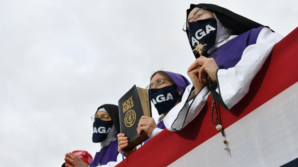 Nuns wearing masks displaying Trump's MAGA slogan listen as US President Donald Trump speaks during a campaign rally at Pickaway Agriculture and Event Center in Circleville, Ohio on October 24, 2020.
