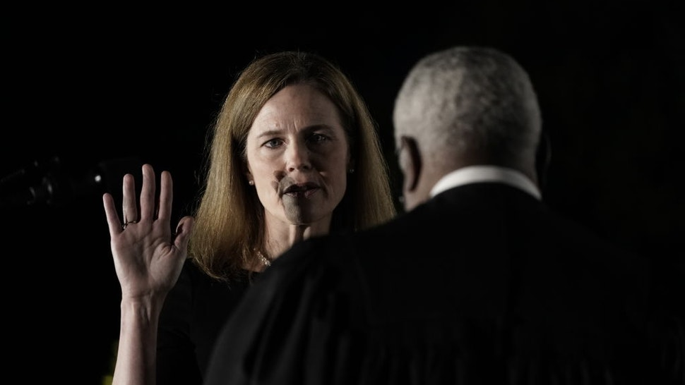 Clarence Thomas, associate justice of the U.S. Supreme Court, right, administers the judicial oath to Amy Coney Barrett, associate justice of the U.S. Supreme Court, during a ceremony on the South Lawn of the White House in Washington, D.C.,