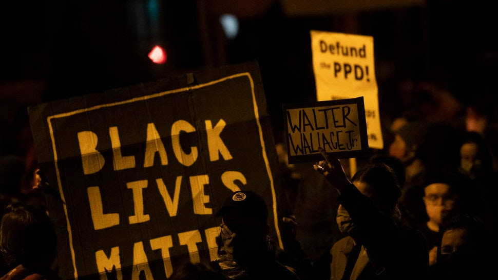 """Demonstrators hold placards reading """"BLACK LIVES MATTER,"""" """"Walter Wallace JR."""" and DEFUND PPD"""" as they gather in protest near the location where Walter Wallace, Jr. was killed by two police officers on October 27, 2020 in Philadelphia, Pennsylvania."""