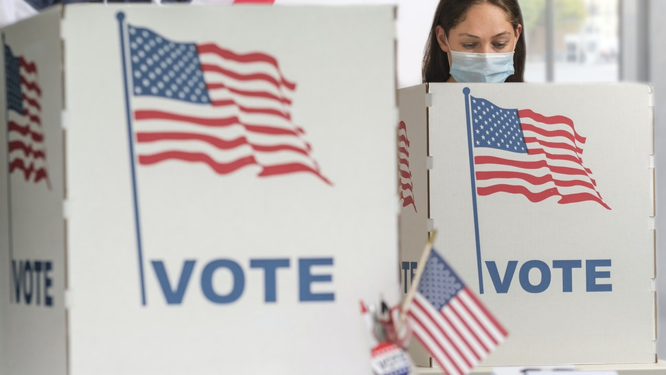 Woman in face mask voting - stock photo