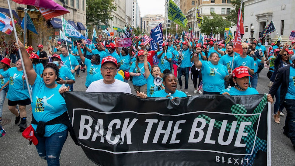 """Members of Blexit march with the message """"Back the Blue"""" after attending a rally on the South Lawn of the White House hosted by U.S. President Donald Trump on October 10, 2020 in Washington, DC."""