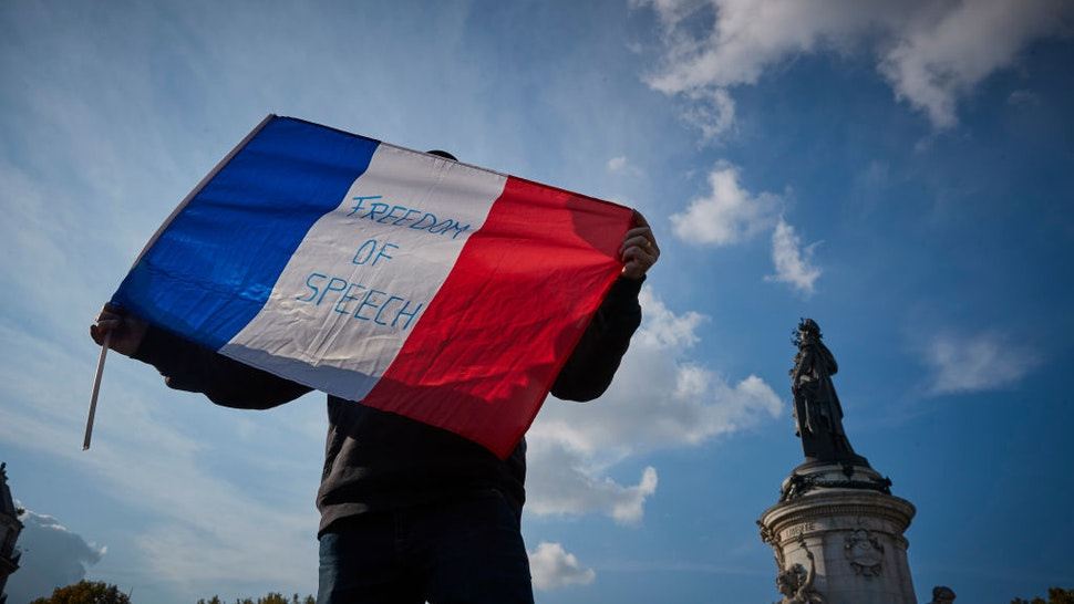 PARIS, FRANCE - OCTOBER 18: A protestor waves a French Tricolor flag with 'Freedom of Speech' written on it during an anti-terrorism vigil at Place de La Republique for the murdered school teacher Samuel Paty who was killed in a terrorist attack in the suburbs of Paris on October 18, 2020 in Paris, France. Thousands of people turned out to show solidarity and express their support for freedom of speech in the wake of Friday's attack. France launched an anti-terrorism investigation after the October 16 incident where police shot the 18 year-old assailant who decapitated the history-geography teacher for having shown a caricature of prophet Mohamed as an example of freedom of speech at the College Bois d'Aulne middle-school. (Photo by Kiran Ridley/Getty Images)