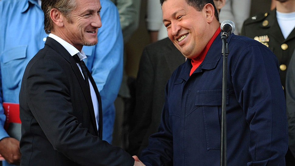 Venezuelan President Hugo Chavez (R) greets US actor Sean Penn after a meeting in Miraflores presidential palace in Caracas on March 5, 2011.