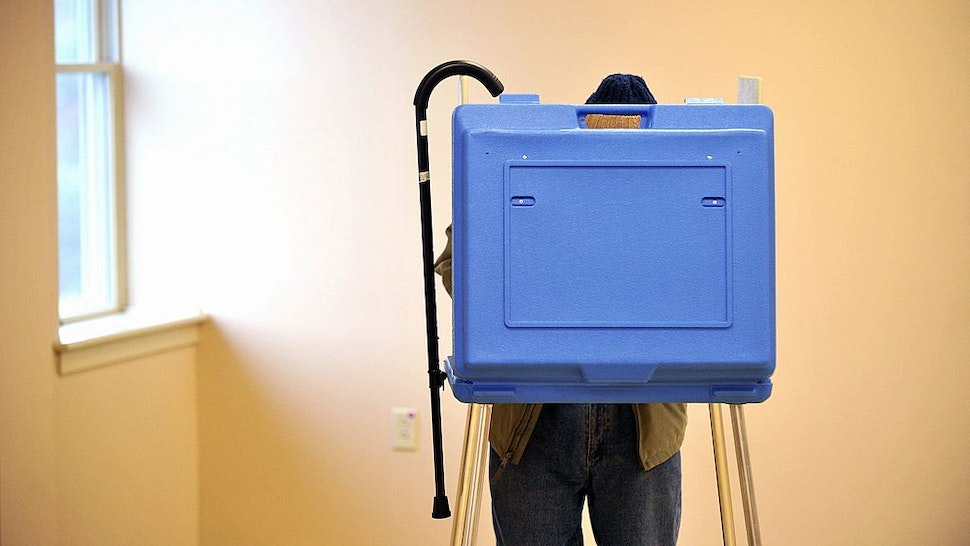 Dave Silverman, 91, hangs his cane on the booth while voting in the State College Evangelical Free Church, in State College, Pennsylvania, Tuesday, November 5, 2013
