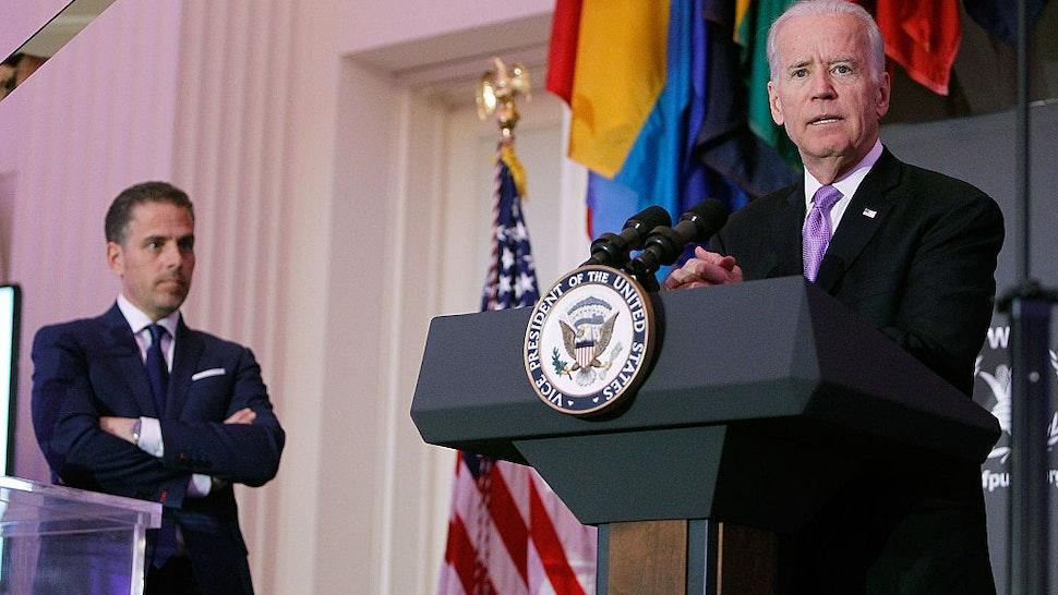 U.S. Vice President Joe Biden (R) speaks as his son, Hunter Biden, looks on at the World Food Program USA's Annual McGovern-Dole Leadership Award Ceremony at Organization of American States on April 12, 2016 in Washington, DC.