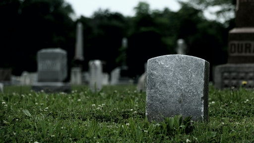 Tombstones On Grassy Field In Cemetery Against Sky - stock photo