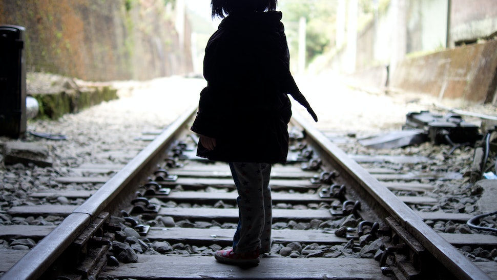Little girl walking on the railroad track of Shengxing Railway Station, Miaoli Taiwan. - stock photo