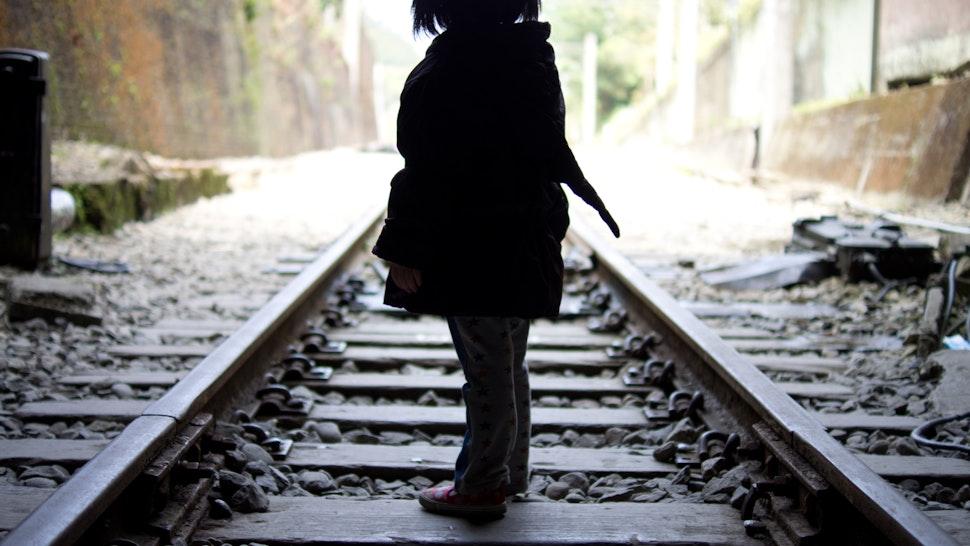 Little girl walking on the railroad track of Shengxing Railway Station, Miaoli Taiwan. - stock photo