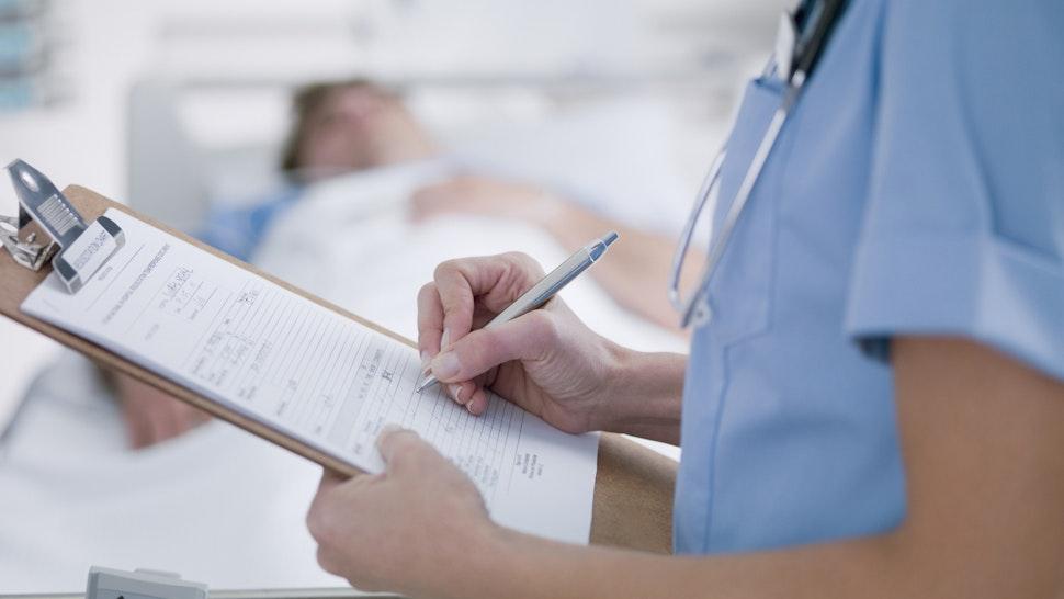 Nurse tending patient in intensive care - stock photo