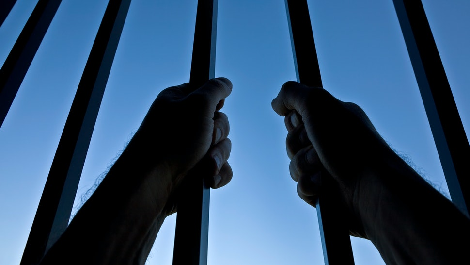 Silhouette of Hands Behind Jail Bars Against Clear Blue Sky - stock photo