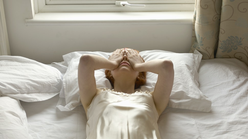 woman on bed with hands over eyes - stock photo