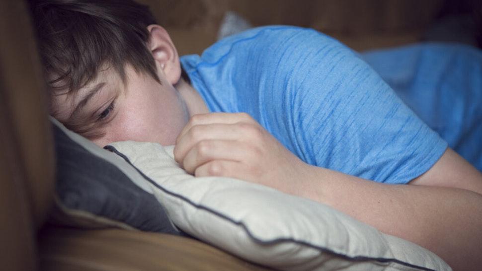 Teenage boy lying on a sofa looking bored