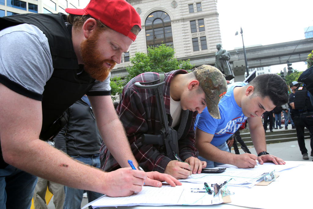 People participating in a guns rights rally sign a petition supporting Washington state Initiative 1621 that would allow people with a concealed pistol license to carry guns in schools during an open carry rally, on May 20, 2018 in Seattle, Washington.