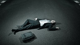 businessman laying on asphalt roadway - stock photo