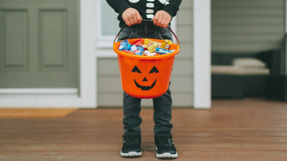 Boy With Sweet Food In Bucket Standing At Home During Halloween