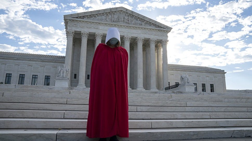 A demonstrator dressed as a character from The Handmaid's Tale stands outside the U.S. Supreme Court as Amy Coney Barrett, U.S. President Donald Trump's nominee for associate justice of the U.S. Supreme Court, meets with Senators at the U.S. Capitol in Washington, D.C., U.S., on Thursday, Oct. 1, 2020. A bruising Senate confirmation fight over Trump's Supreme Court choice may seal the fates of several incumbent senators in the November election, though it has yet to drastically alter the odds for which party will control the chamber.