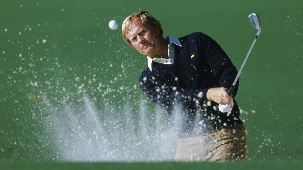 Jack Nicklaus of the USA keeps his eye on the ball as he hits out of the bunker with the sand creating a crown effect during the US Masters Golf Tournament on 12th April 1986 at the Augusta National Golf Club in Augusta, Georgia, USA. Visions of Sports.