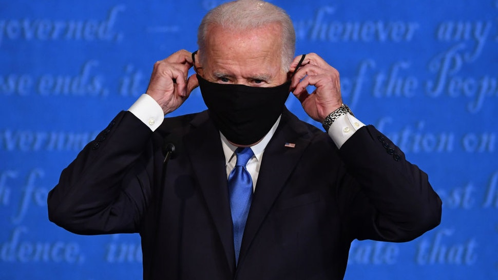 Joe Biden, 2020 Democratic presidential nominee, puts on a protective mask during the U.S. presidential debate at Belmont University in Nashville, Tennessee, U.S., on Thursday, Oct. 22, 2020. Trump and Biden traded charges of secretly taking money from foreign interests, after the former vice president addressed head-on Trump's efforts to portray him as corrupt. Photographer: Kevin Dietsch/UPI/Bloomberg