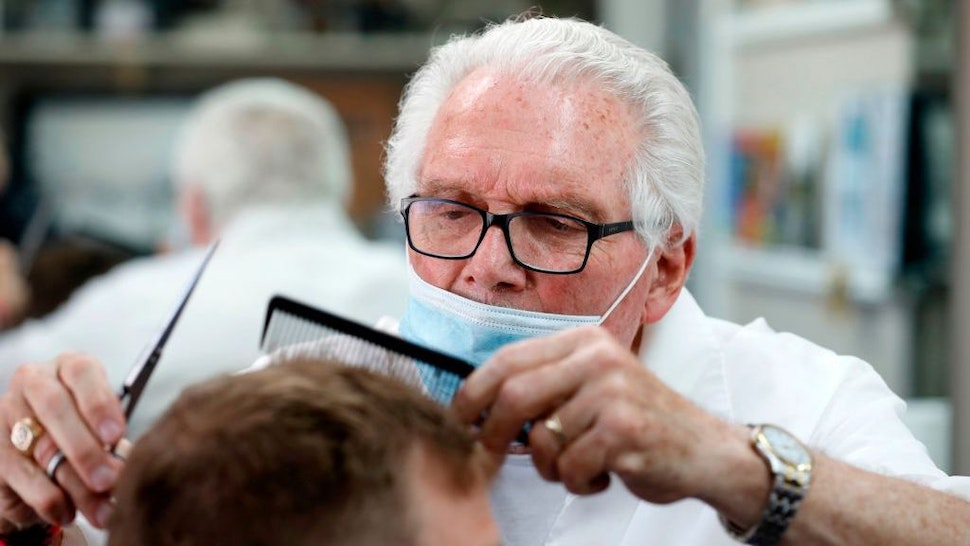 Barber Karl Manke who faces two misdemeanor charges for reopening his shop despite state shutdown orders, cuts a client's hair at his barber shop on May 12, 2020 in Owosso, Michigan. - The most defiant challenge of Michigan Gov. Gretchen Whitmers pandemic-prompted restrictions on businesses has not come from a titan of industry but from a 77-year-old barber and occasional novelist in a small town between Lansing and Flint. (Photo by JEFF KOWALSKY / AFP) (Photo by JEFF KOWALSKY/AFP via Getty Images)