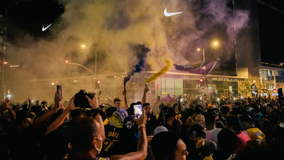 Lakers fans celebrate in front of the Staples Center on October 11, 2020 in Los Angeles, California. People gathered to celebrate after the Los Angeles Lakers defeated the Miami Heat in Game 6 of the NBA Finals. (Photo by Brandon Bell/Getty Images)