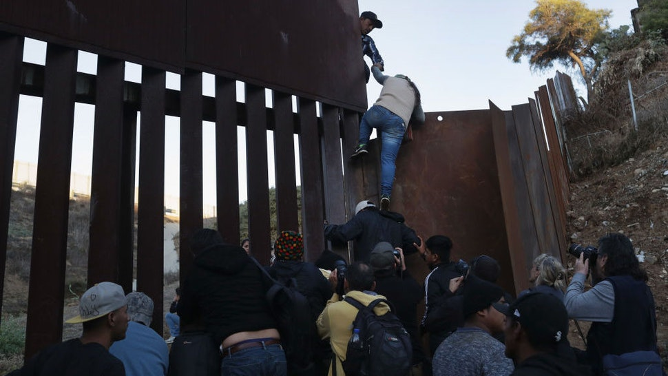 A woman climbs atop a fellow member of the migrant caravan while crossing over the U.S.-Mexico border fence on December 2, 2018 from Tijuana, Mexico. Numerous members of the caravan were able to pass from Tijuana to San Diego and were quickly taken into custody by U.S. Border Patrol agents. Most had planned to request political asylum in the United States after traveling more than 6 weeks from Central America. (Photo by John Moore/Getty Images)