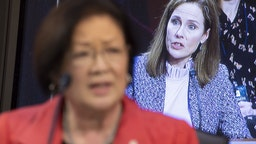 Amy Coney Barrett, U.S. President Donald Trump's nominee for associate justice of the U.S. Supreme Court, is displayed on a television monitor as Senator Mazie Hirono, a Democrat from Hawaii, left, speaks during a Senate Judiciary Committee confirmation hearing in Washington, D.C., U.S., on Wednesday, Oct. 14, 2020. Senate Democrats entered a second day of questioning Barrett having made few inroads in their fight to keep her off the Supreme Court and elicited few clues about how she would rule on key cases. Photographer: Michael Reynolds/EPA/Bloomberg
