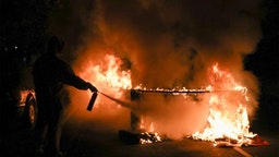 A person uses a fire extinguisher to put out a burning barricade in Philadelphia on October 27, 2020, during a protest over the police shooting of 27-year-old Black man Walter Wallace. - Hundreds of people demonstrated in Philadelphia late on October 27, with looting and violence breaking out in a second night of unrest after the latest police shooting of a Black man in the US. The fresh unrest came a day after the death of 27-year-old Walter Wallace, whose family said he suffered mental health issues. On Monday night hundreds of demonstrators took to the streets, with riot police pushing them back with shields and batons. (Photo by Gabriella AUDI / AFP)