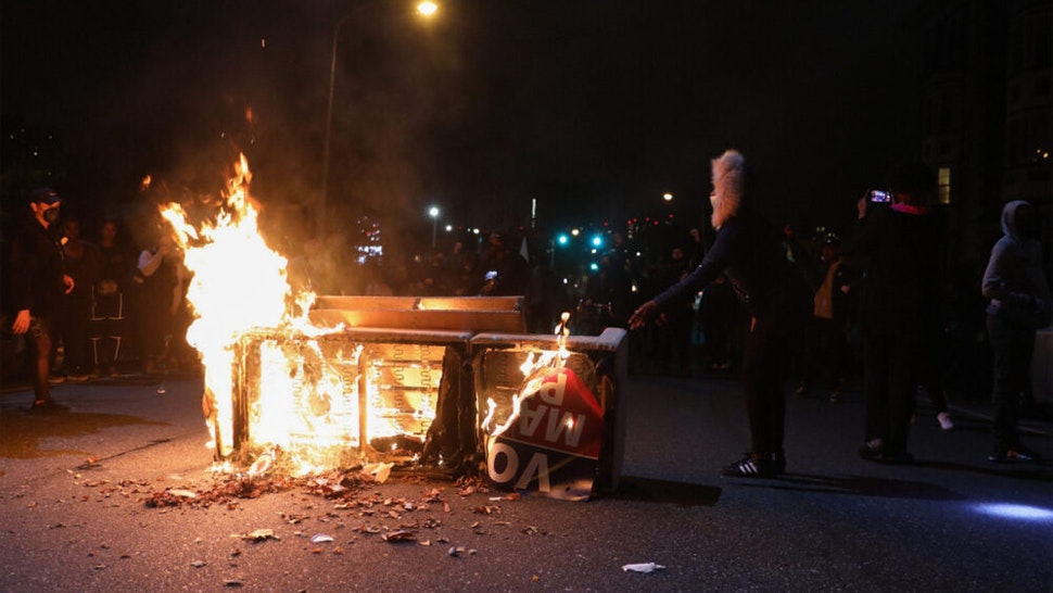 Demonstrators stand near a burning barricade in Philadelphia on October 27, 2020, during a protest over the police shooting of 27-year-old Black man Walter Wallace. - Hundreds of people demonstrated in Philadelphia late on October 27, with looting and violence breaking out in a second night of unrest after the latest police shooting of a Black man in the US. The fresh unrest came a day after the death of 27-year-old Walter Wallace, whose family said he suffered mental health issues. On Monday night hundreds of demonstrators took to the streets, with riot police pushing them back with shields and batons.