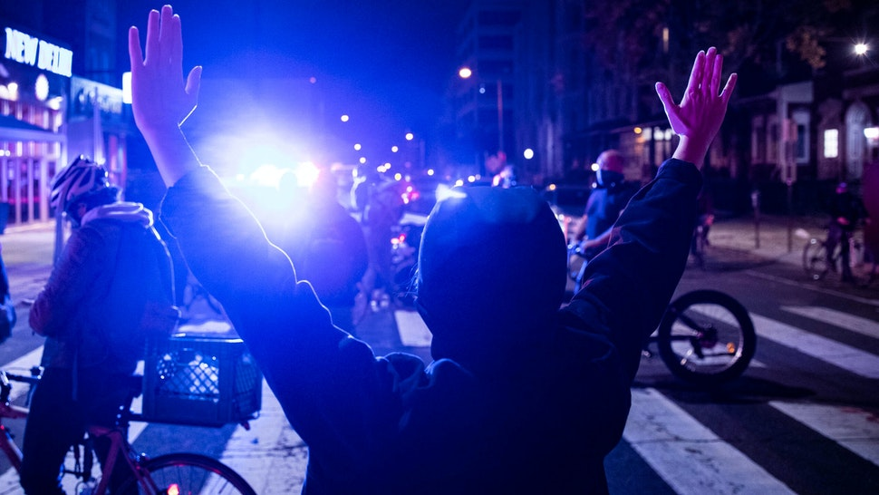 A protester raises their hands in West Philadelphia on October 27, 2020, during a demonstration against the fatal shooting of 27-year-old Walter Wallace, a Black man, by police. - Hundreds of people demonstrated in Philadelphia late on October 27, with looting and violence breaking out in a second night of unrest after the latest police shooting of a Black man in the US. The fresh unrest came a day after the death of 27-year-old Walter Wallace, whose family said he suffered mental health issues. On Monday night hundreds of demonstrators took to the streets, with riot police pushing them back with shields and batons.