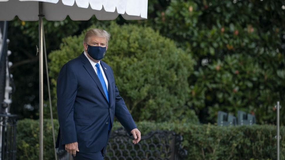U.S. President Donald Trump wears a protective mask while walking to the South Lawn of the White House before boarding Marine One in Washington, D.C., U.S., on Friday, Oct. 2, 2020. Trump will be taken to Walter Reed National Military Medical Center to be treated for Covid-19, the White House said. Photographer: Sarah Silbiger/Bloomberg