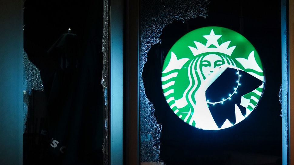 A man walks past a vandalized Starbucks during a protest on May 29, 2020 in Atlanta, Georgia. Demonstrations are being held across the US after George Floyd died in police custody on May 25th in Minneapolis, Minnesota.