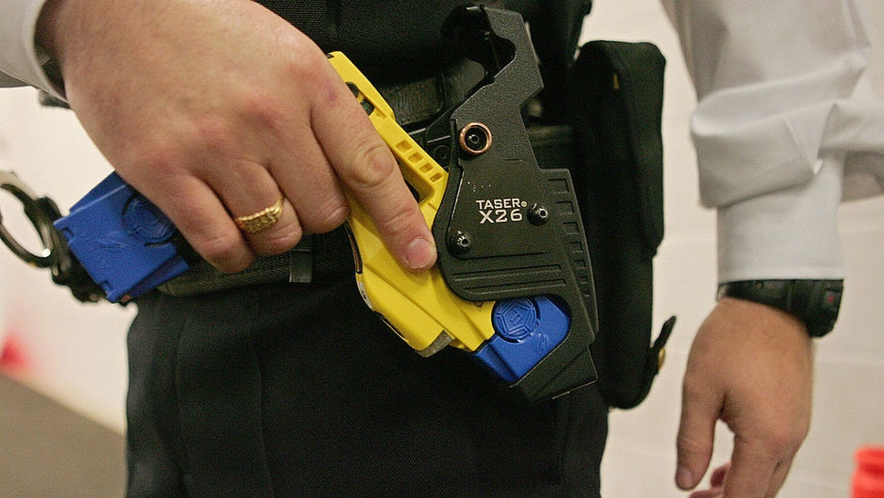 A British police officer holsters a taser gun during a training session at the Metropolitan Police Specialist Training Centre, in Gravesend, Kent, in south-east England, 05 December 2007. Taser guns are to be issued to London's Metropolitan Police from Monday 10 December 2007. AFP PHOTO/CARL DE SOUZA/FILES