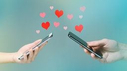 Young man and woman's hands holding smart phones with hearts floating over (PM Images/Getty Images)