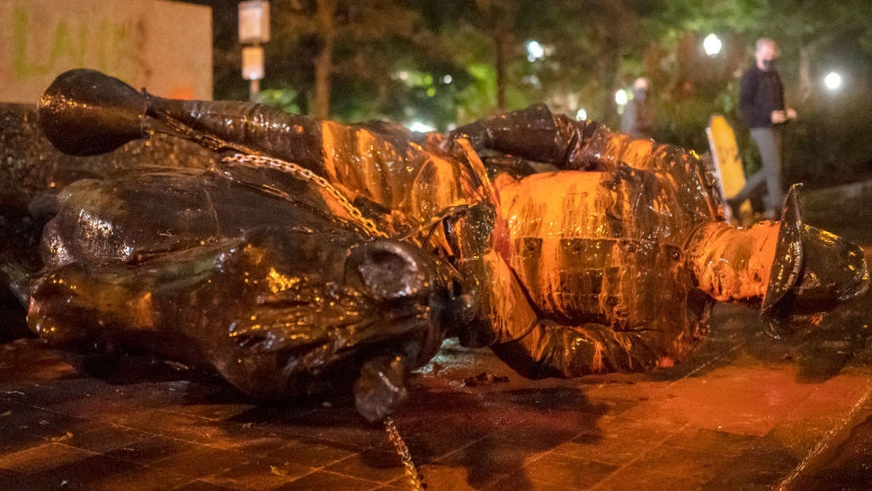 PORTLAND, OR - OCTOBER 11: Protesters walk past a toppled statue of President Theodore Roosevelt during an Indigenous Peoples Day of Rage protest on October 11, 2020 in Portland, Oregon. Protesters tore down statues of two U.S. presidents and broke windows out of downtown businesses Sunday night before police intervened. (Photo by Nathan Howard/Getty Images)